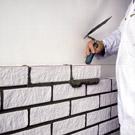Ausrichten und Anklopf- en des Verblenders an der Mauerschnur.